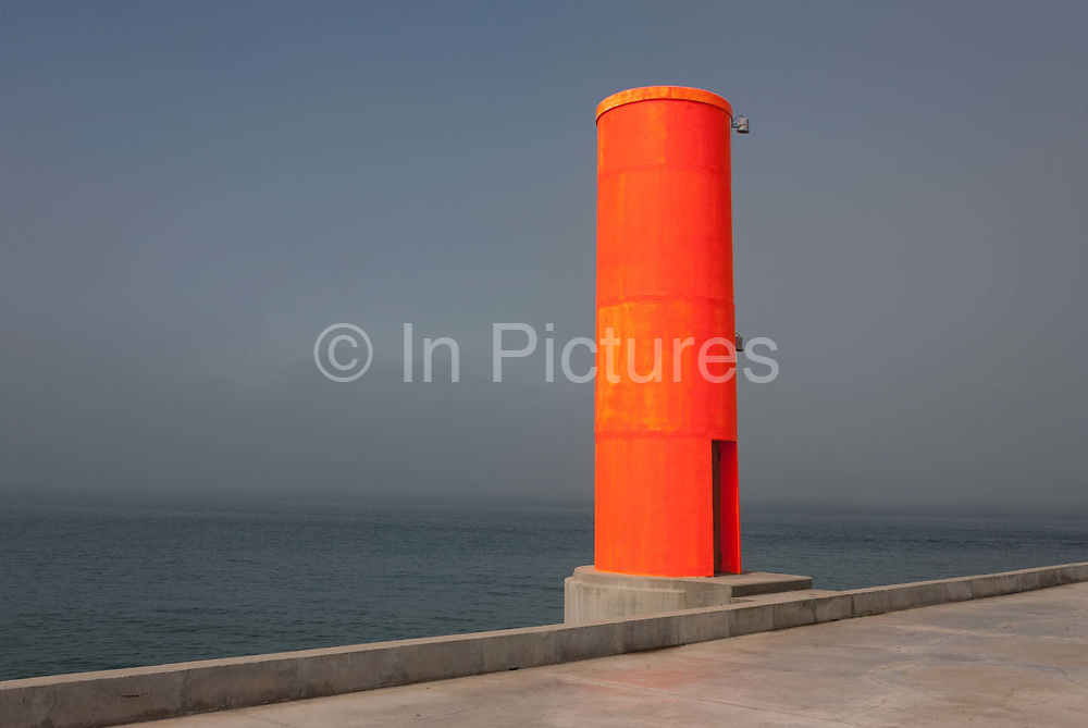 A weird landscape of the concrete, fluorescent-coloured shipping navigation marker a few hundred metres out from the beach on the artificial pier, on 18th July 2016, on Paredao da Praia da Barra, at Barra, near Aveira, Portugal. Visible to shipping many miles from the coast, the marker aides vessels to find their route from the open sea and through the narrow channel into the industrial port of Aveiro.