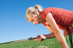Girl (10-11) in meadow looking through magnifying glass, side view