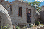 Doug Camblin, the current owner, in the doorway of the ruins of the main living room at Carraro's Grotto in Yarnell, Arizona.