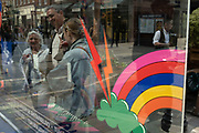 People in Covent Garden district interact with a brightly coloured window display for Sunglasses Hut on a street corner on 26th May 2021 in London, United Kingdom. Symbols of weather have been painted onto the windows depicting rainbows, lightening strikes, clouds and rain drops.
