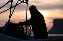 © Licensed to London News Pictures. <br /> 24/04/2015. <br /> <br /> Saltburn, United Kingdom<br /> <br /> Lesley Jefferson stacks lobster pots on board the fishing boat Ellen before heading out to sea. The Ellen is the last remaining commercial fishing boat working out of Saltburn.<br /> <br /> <br /> <br /> Photo credit : Ian Forsyth/LNP