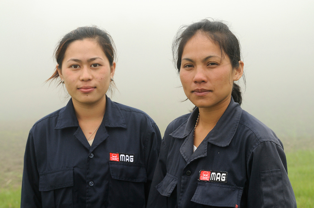 """Mines Advisory Group, Technicians, Sia Thorthongyer, age 19 (left) and Vonekham Dalavong, age 29 (right), take their dangerous jobs seriously, but find humor is sometimes the best way to avoid stress.  They joke about the perils of 12 women trying to share one bathroom in the morning.  Sia said, """"Sometimes we are all standing crossed legged in the que pounding on the door yelling emergency with threats for who ever is in the bathroom.  Sometimes we just run to a bush.""""..Laos was part of a """"Secret War"""", waged within its borders primarily by the USA and North Vietnam.  Many left over weapons supplied by China and Russia continue to kill.  However, between 90 and 270 million fist size cluster bombs were dropped on Laos by the USA, with a failure rate up to 30%.  Millions of live cluster bombs still contaminate large areas of Laos causing death and injury..The US Military dropped approximately 2 million tons of bombs on Laos making it, per capita, the most heavily bombed country in the world.   ..The women of Mines Advisory Group (MAG) work everyday under dangerous conditions removing unexploded ordinance (UXO) from fields and villages...***All photographs of MAG's work must include (either on the photo or right next to it) the credit as follows:  Mine clearance by MAG (Reg. charity)***."""