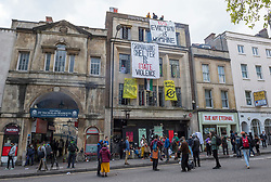 """© Licensed to London News Pictures; 01/05/2021; Bristol, UK. A building now called """"40A"""" has been squatted on the High Street in Bristol city centre, and today banners including one saying """"Criminalising shelter is state violence"""" have been hung on the building and people gathered outside in the roadway following the annual MayDay trade union march and rally for workers rights through the city centre. A small number of Kill the Bill protesters had joined the trade union rally, and a woman said that laws against squatting will increase if the Police Crime Sentencing and Courts bill, which the Kill the Bill protests are against, is passed into law. The squatters have given legal papers to go to court on 07 May. Photo credit: Simon Chapman/LNP."""