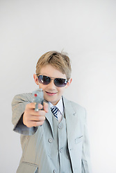 Boy holding toy gun and playing gangster, smiling