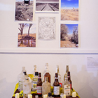 """Liquor bottles, drawings and photographs form an alter in one of the multi-media installments in the """"Exposure"""" exhibit at Art123 Gallery in Gallup Thursday."""