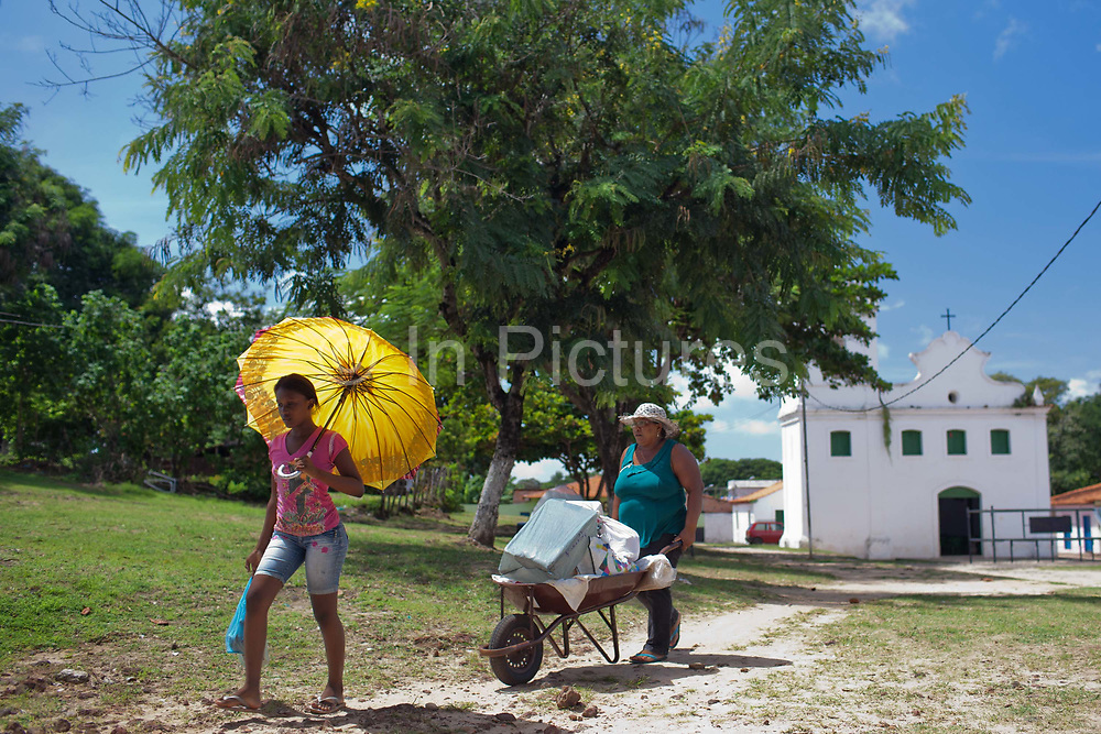 Two women walking in the midday sun in Alcantara on 27th May 2014, Maranhao, Brazil. It is an island off the north east coast of Brazil close to Sao Luis, state capital of, and is one of the largest Quilombos in Brazil, which are communities that were originally set up by escaped or freed slaves during the colonial period.