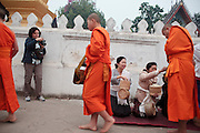 "15 MARCH 2009 -- LUANG PRABANG, LAOS: A tourist in Luang Prabang, Laos, photographs Buddhist Monks as they go about their ""Tak Bat,"" Lao for ""monks morning rounds."" The monks collect alms in the form of food from people who line their route. For the monks, it is the only food they get that day, for the people it's a chance to ""make merit."" Luang Prabang is a UNESCO World Heritage Site and the spiritual capital of Laos. There are dozens of ""wats"" or temples and thousands of monks in the city. It is still the center of Buddhist education in Laos. Photo By Jack Kurtz"