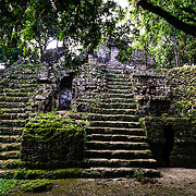 One of the building only partially restored and covered in moss and plants in the Tikal Maya ruins in northern Guatemala, now enclosed in the Tikal National Park.
