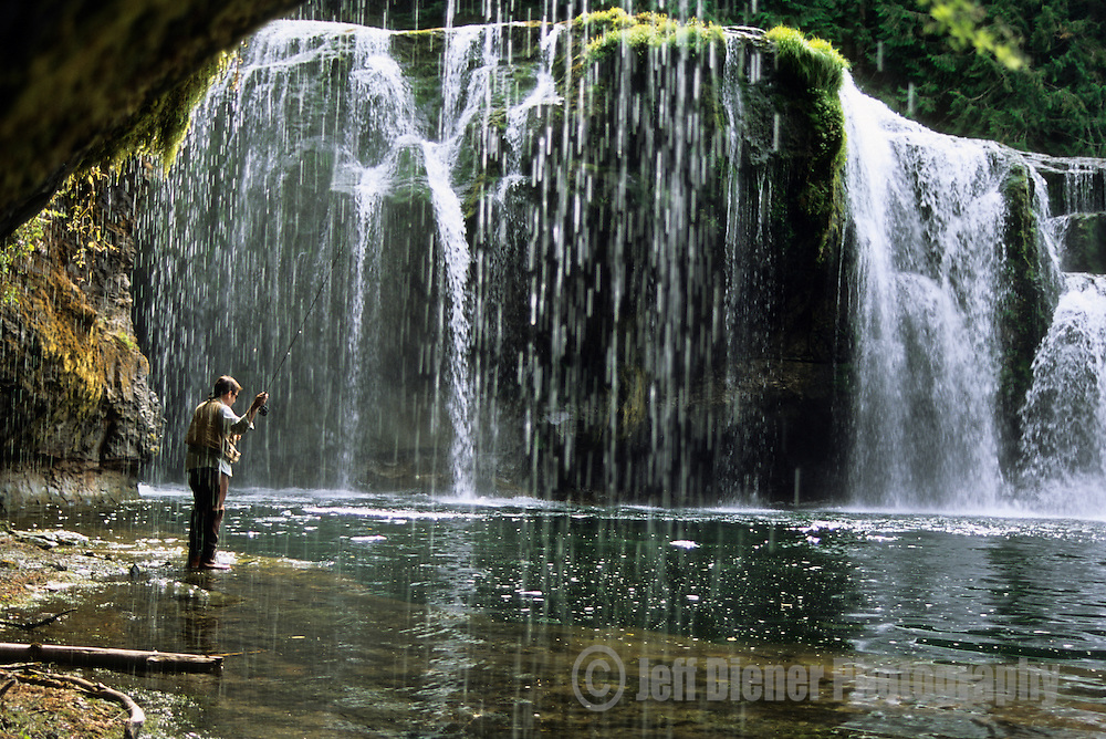 A young man fly fishes below Lewis Falls on the Lewis River in Washington.