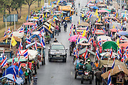 21 FEBRUARY 2014 - KHLONG CHIK, PHRA NAKHON SI AYUTTHAYA, THAILAND:  A truck drives between farmers' tractors blocking Highway 32 near Bang Pa In in Phra Nakhon Si Ayutthaya province. About 10,000 Thai rice farmers, traveling in nearly 1,000 tractors and farm vehicles closed the road. The farmers were traveling to the airport in Bangkok to protest against the government because they haven't been paid for rice the government bought from them last year. The farmers turned around and went home after they met with government officials who promised to pay the farmers next week. This is the latest blow to the government of Yingluck Shinawatra which is confronting protests led by anti-government groups, legal challenges from the anti-corruption commission and expanding protests from farmers who haven't been paid for rice the government bought.   PHOTO BY JACK KURTZ