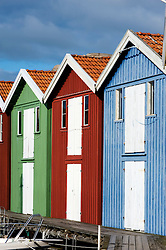 Brightly colored boathouses in harbour at Smogen on Sweden`s west Bohuslan Coast