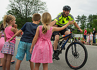 Officer Jim McIntire gives youngsters a high five as the parade heads down Park Street on Saturday morning to start the Old Home Day festivities at Pines Park.  (Karen Bobotas/for the Laconia Daily Sun)