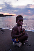 Young Ni-Vanuatu kids play at the beach until dark, playing in the water and football on the black volcanic sand beach.