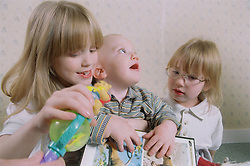 Two young sisters playing with baby brother,