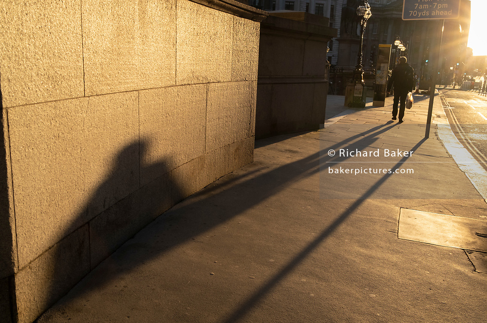 With most Londoners still working from home, a commuter leaves their shadow on a wall of Royal Exchange while walking along a quiet Threadneedle Street during the evening rush-hour during the third lockdown of the Coronavirus in the City of London, the capital's financial district, on 26th February 2021, in London, England.