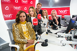 Spice Girls (left to right) Melanie Brown, Melanie Chisholm, Geri Horner and Emma Bunton during a live appearance this morning on the Heart Breakfast show with host Jamie Theakston at Global Radio in Leicester Square, London.