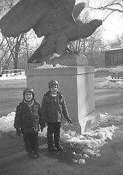 two boys standing in front of a statue in New York