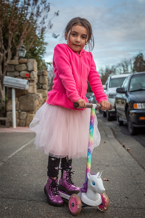"""""""I think the mask is good to protect us from the germs.""""  -Five year old Marbella Garcia rides her unicorn scooter in front of her home on Dena Street in Calistoga."""