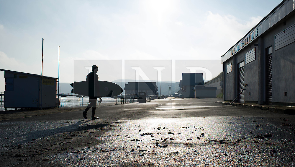 © Licensed to London News Pictures. 07/09/2013<br /> <br /> Saltburn, Cleveland, England<br /> <br /> A surfer makes his way over the lower promenade littered with stones and rubbish following an evening of torrential rainfall that caused flooding and disruption to Saltburn in Cleveland.<br /> <br /> Photo credit : Ian Forsyth/LNP