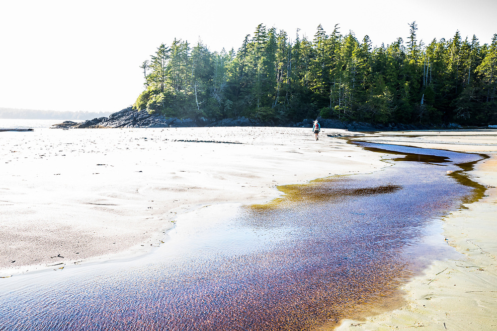A woman walking on a beach near Tofino on Middle beach, Vancouver Island, British Columbia, Canada.