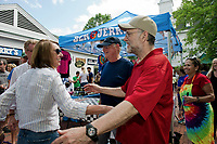 Rusty McLear and Jodie Herbert get a hug from Ben Cohen and Jerry Greenfield during Ben & Jerry's grand opening at Meredith's Mill Falls Marketplace on Saturday afternoon.   (Karen Bobotas/for the Laconia Daily Sun)