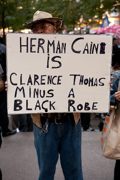 "An African-American man with a sign reading ""Herman Cain is Clarence Thomas minus a black robe."""