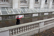 A tourist walks along Whitehall carrying a transparent and red umbrella with the words I Love Rain, on 19th October 2017, in London, England.