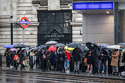 © Licensed to London News Pictures. 20/10/2020. London, UK. Large queues form at Victoria Tube Station, London as commuters brave the wind and rain on their way to work as storm Barbara hits the UK with winds over 40mph and heavy rain. The Met Office have issue a yellow weather warning for torrential rain and flooding for the South East of England as a storm from Spain heads to the UK. Photo credit: Alex Lentati/LNP