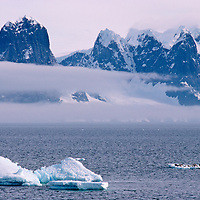 ANTARCTICA. Seals sleep on iceberg under mountains on Wienke Island, in South Shetland Islands near the Antarctic Peninsula.