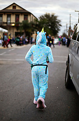30 January 2016. New Orleans, Louisiana.<br /> A parader heads to the the mico-Krewe of 'Tit Rex' parade in the Bywater and Marigny. All the floats are scaled down versions of the current parade giant with a shoe box at their base. The theme for this year's parade was 'No Big Deal.' <br /> Photo©; Charlie Varley/varleypix.com