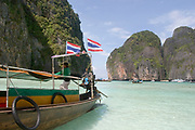 Longtail boats at the World famous Maya Bay on Phi Phi Ley. This is where Leonardo di Caprio swam during the movie, The Beach. Now tourists arrive in their hundreds to sit on the same white sand and swim in the same waters. Pure white sand and crystal clear water prove a strong attraction.