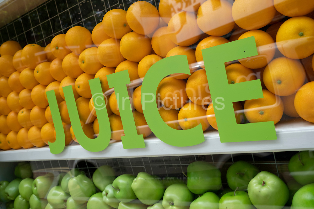 Apples and oranges in the window of a juice bar on 2nd June 2020 in Birmingham, United Kingdom. A juice bar is an establishment that primarily serves prepared juice beverages such as freshly squeezed or extracted fruit juices, juice blends.