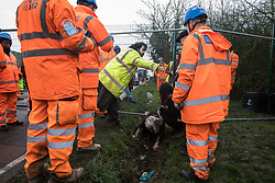 Harefield, UK. 8 February, 2020. HS2 engineers look on as an elderly activist crawls through a ditch under a road closure on Harvil Road in the Colne Valley implemented to facilitate tree felling works for the high-speed rail link. Environmental activists based at a series of wildlife protection camps in the area prevented the tree felling works for the duration of the weekend for which they were scheduled.