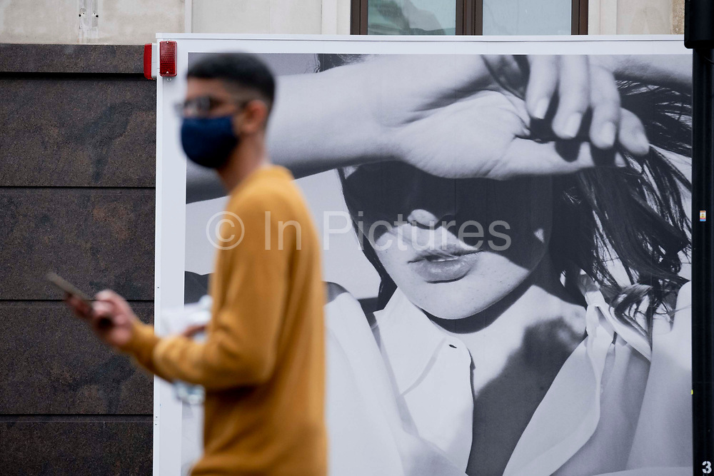 A shopper wearing a face mask walks beneath a large billboard for a fashion retailer on Oxford Street, on 8th July 2021, in London, England.