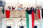 Kuwaiti woman wave from rooftops as they celebrate following the liberation of Kuwait from Iraqi occupation by coalition forces February 28, 1990 in Kuwait City, Kuwait.