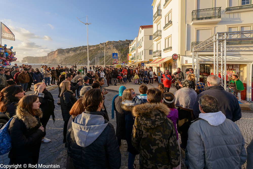 Nazaré, Portugal - February 12, 2018 - Nazaré Festival 01 - A band plays music for the crowd at the beach in Nazare. Carnaval is celebrated in Nazare and throughout Portugal. Costumed parades and plenty of music! <br /> <br /> Image: © Rod Mountain<br /> <br /> http://www.rodmountain.com<br /> http://bit.ly/Nazaré_bw<br /> http://bit.ly/Nazare_Portugal<br /> <br /> Nikon D800 / Nikkor Lens<br /> @nikoncanada #NikonCA<br /> @NikonUSA #NikonNoFilter<br /> @nikoneurope #NikonEurope<br /> <br /> https://www.visitportugal.com/en<br /> @visitportugal <br /> <br /> https://en.wikipedia.org/wiki/Nazaré,_Portugal<br /> http://www.cm-nazare.pt/en<br /> @municipiodanazare @cmnazare @CMNazareMata <br /> <br /> #turismoemportugal #turismo #rotaportugal <br /> #awesomebnw #folkgood #traveldeeper #tourism<br /> <br /> #worldcaptures #justgoshoot #TheGlobeWanderer #CantSkipPortugal #travelblog#zonestreet #ourstreets #carnaval #colour #outdoors #friendsinstreets #featuremeinstagood #travelblog#instago<br /> <br /> <br /> https://en.wikipedia.org/wiki/Carnival <br /> https://en.wikipedia.org/wiki/Portugal