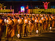 """22 FEBRUARY 2016 - KHLONG LUANG, PATHUM THANI, THAILAND: Buddhist monks participate in the candle light procession around the chedi during the Makha Bucha Day service at Wat Phra Dhammakaya.  Makha Bucha Day is a public holiday in Cambodia, Laos, Myanmar and Thailand. Many people go to the temple to perform merit-making activities on Makha Bucha Day, which marks four important events in Buddhism: 1,250 disciples came to see the Buddha without being summoned, all of them were Arhantas, Enlightened Ones, and all were ordained by the Buddha himself. The Buddha gave those Arhantas the principles of Buddhism, called """"The ovadhapatimokha"""". Those principles are:  1) To cease from all evil, 2) To do what is good, 3) To cleanse one's mind. The Buddha delivered an important sermon on that day which laid down the principles of the Buddhist teachings. In Thailand, this teaching has been dubbed the """"Heart of Buddhism."""" Wat Phra Dhammakaya is the center of the Dhammakaya Movement, a Buddhist sect founded in the 1970s and led by Phra Dhammachayo.      PHOTO BY JACK KURTZ"""