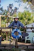 Senior adult fisherman business owner stands on pier.