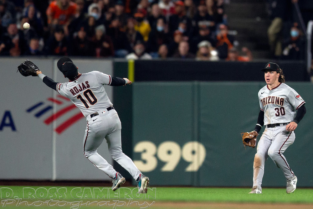 Arizona Diamondbacks shortstop Josh Rojas (10) makes an over-the-shoulder catch of San Francisco Giants' Steven Duggar's popup in front of center fielder Jake McCarthy (30) during the sixth inning of a baseball game, Tuesday, Sept. 28, 2021, in San Francisco. (AP Photo/D. Ross Cameron)