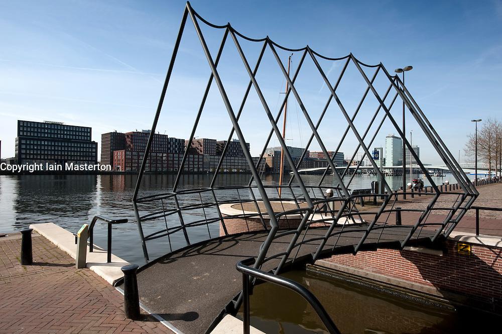 Modern steel footbridge crossing canal in modern Java Island district of Amsterdam Netherlands