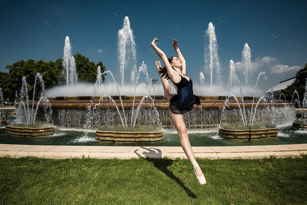 Ballerina jumping in front of fountain