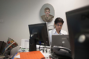 A lady concentrates in a cluttered office unit beneath corporate artwork in Ernst & Young's Norman Foster-designed building. The oval-shaped picture depicts an esasperated-looking female rolling her eyes to the ceiling while her contemporary below stares down at her laptop surrounded by the paraphernalia of her accounting London job. Dressed in an open-neck shirt and wearing glasses, the woman at work is busy and preoccupied with the job in hand of auditing a company's accounts. Despite all the 385,000 square feet in the European headquarters on the River Thames, there is no spare space in this tiny office that she shares with another employee. The Fine Art has been supplied by Anderson O'Day and E & Y have invested in 500,000 Pounds of office art for their 114,000 employees in 700 locations across 140 countries around the world.