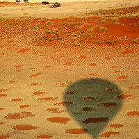 Africa, Namibia, Sossusvlei. Aerial view of red dunes, grasses, and fairy circles dotting the landscape of the NamibRand Nature Reserve by hot air balloon. It is still unkonwn exactly how and why the fairy circles have formed.