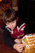 Boy age 7 wearing a UK Union Jack flag shirt decorating a Christmas gingerbread house. St Paul Minnesota USA