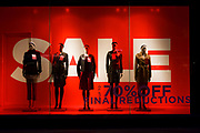 Giant letters lure potential customers into this branch of Hobbs with a Sale offer sign. Their mannequins are seen in the window of London's Long Acre (street) clothing shop - a line-up of womens' fashion variations displayed in the window on a winter's afternoon. Further reductions are also promised if the potential customer enters the store. With an economic recession taking hold on Britain's high streets and exclusive retail outlets, deals and offers are vital to keep spending and turnover up.