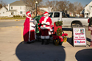 "05 DECEMBER 2020 - INDIANOLA, IOWA: STAN THOMPSON and his wife, EILEEN THOMPSON, dressed as Santa Claus and Mrs. Claus, wait for a carload of children during a drive through visit with Santa Claus. This is the seventh year the Thompsons have dressed as the Clauses to entertain the children of Indianola. About 500 children visited Santa Claus and Mrs. Claus in Indianola Saturday. The town has hosted Santa on the town square for the last seven years but the COVID-19 (SARS-Cov-2) pandemic forced organizers to move the event to the parking lot of a local hardware store and do it ""drive through"" style. Iowa has one of the highest Coronavirus test rates in the United States.        PHOTO BY JACK KURTZ"