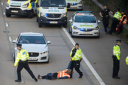 Ockham, UK. 21st September, 2021. A Surrey Police officer drags an Insulate Britain climate activist from the anticlockwise carriageway of the M25 between Junctions 9 and 10 where they had been protesting as part of a campaign intended to push the UK government to make significant legislative change to start lowering emissions. Both carriageways were briefly blocked before being cleared by Surrey Police. The activists are demanding that the government immediately promises both to fully fund and ensure the insulation of all social housing in Britain by 2025 and to produce within four months a legally binding national plan to fully fund and ensure the full low-energy and low-carbon whole-house retrofit, with no externalised costs, of all homes in Britain by 2030.