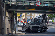 The damaged remains of a lorry near a scrap metal yard at Loughborough Junction after it crashed into one of the railway bridges - a main transport route for commuters into the City, on 8th May 2018, in south London, England. One person was injured.
