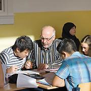 Nederland Rotterdam 23-09-2009 20090923 Foto: David Rozing  Serie over onderwijs, het Libanon Lyceum Kralingen,  openbare scholengemeenschap voor mavo, havo en vwo.   Lesuur wiskunde. Een leraar behandelt de leerstof, geeft uitleg aan een groepje leerlingen tijdens het zelfstandig klassikaal werken.  Lesuur wiskunde.  , toekomst, toelichten, toelichting geven, uitleg, uitleg geven, uitleggen, vaardigheden, vaardigheid, voor de klas staan, voortgezet, vut, writing, young, Youth, zachte sector, zelfstandig werken, , resultaten samenstelling, samen, samenstelling, scholen, scholengemeenschap, scholier, scholieren, scholing, school, schoolbank, schoolbankje, schooljaar, schoolprestaties, schools, schoolse, schoolse situatie, schrift, schriftelijk, schriftelijke, schrijven, senior, senioren, seniors, socialize, socializing, student, students, studeren, studie, studieboek, studies, studieuur, study, studying, teacher, teaching, tekst, the netherlands, vinger in de lucht houden, vinger in de lucht steken, vinger opsteken, vragen                                                      .Foto: David Rozing