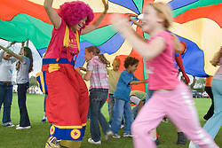 Clown taking part in a parachute game with a group of children at a Parklife summer activities event,